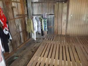 Kambodscha | Koh Kchhang Fishing Village Wohnung. Einfache Bretter aus Holz dienen als Bett und ein paar Kleider auf der Stange stellen den Kleiderschrank dar