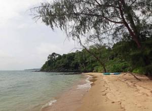 Kambodscha | Koh Thmei Kanutour zur gegenüber liegenden Insel Koh Seh. Unser blau weiß türkisfarbenes Kanu liegt am Strand gesäumt von grünem Urwald