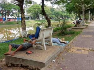 Kambodscha |Mittagspause der Einheimischen am Fluss in Siem Reap. Männer liegen schlafend am Boden und auf Bänken am Flussufer