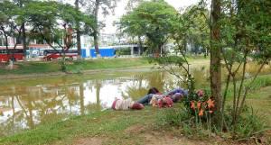 Kambodscha |Mittagspause der Einheimischen am Fluss in Siem Reap. Frauen schlafen im Gras am Flussufer