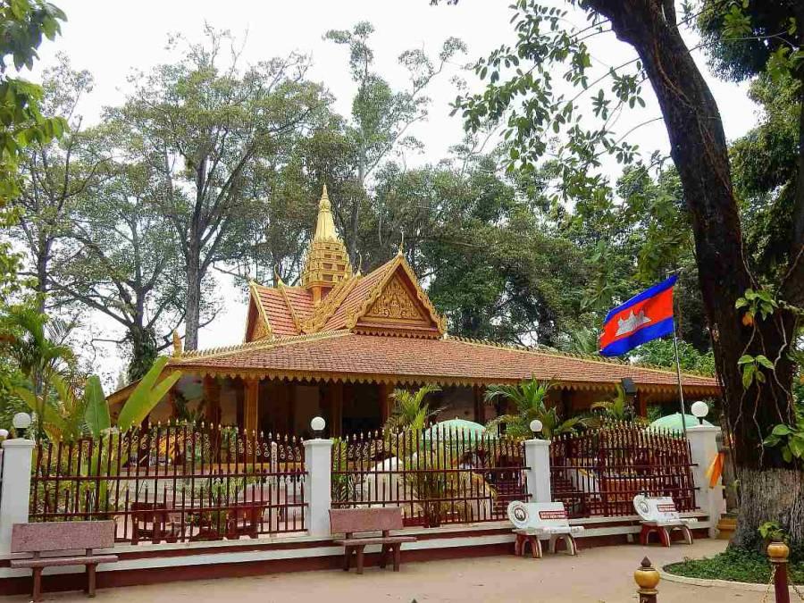 Kambodscha | Königspalast in Siem Reap. Goldgesäumtes Dach eines flachen Hauses hinter einem Zaum mit der Kambodscha Fahne im Vordergrund