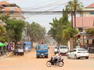 Kambodscha | Einer unserer Tipps, die Straßen in Siem Reap abseits des Tourismus und Sehenswürdigkeiten zu besuchen. Staubige Schotterpiste mit einfachen Häusern, gesäumt von Palmen