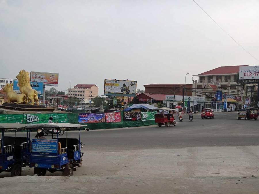 Kambodscha | Das Monument der Golden Lion im Hauptkreisverkehr in Sihanoukville. Einige Tuk Tuks und Roller im Vordergrund
