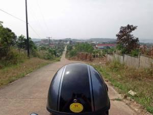 Kambodscha | Moped Tour durch Sihanoukville. Hennings Helm von hinten mit Blick auf die gerade lange Straße im Hinterland gesäumt von ein paar Häusern