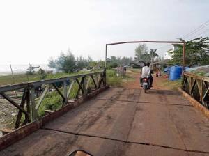 Kambodscha | Straße vom Ortes Beach nach Sihanoukville über eine Brücke und Pistenstraße. Zwei Männer auf einem Moped in der Mitte.