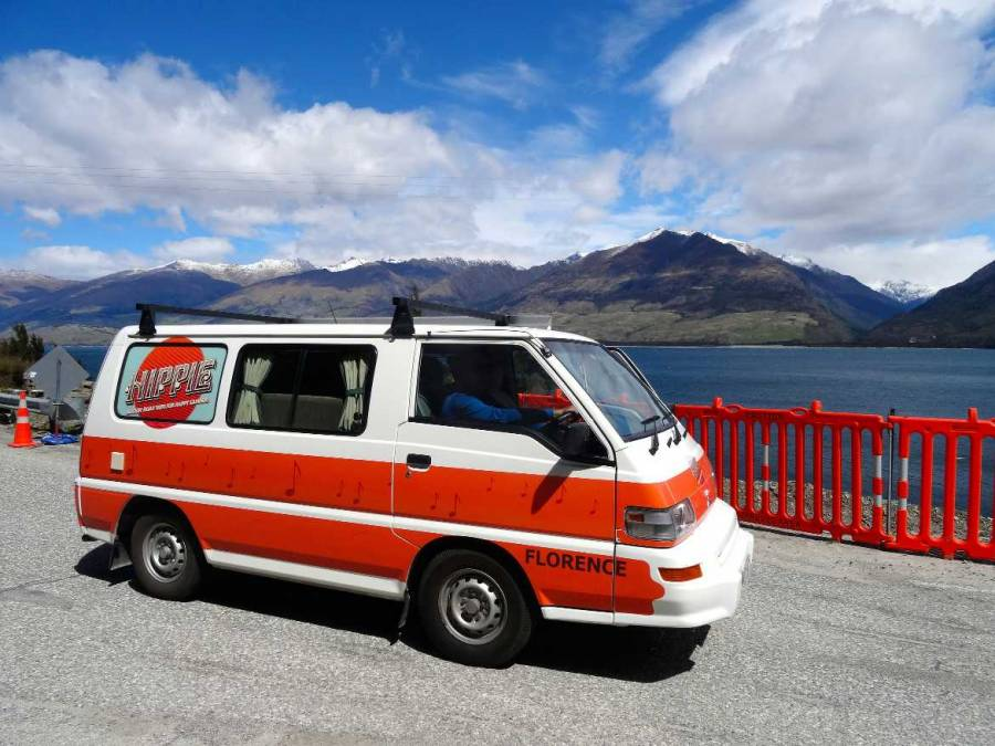Neuseeland | Camper von Apollo: Hippie Florence. Unser orange-weißer Camper vor einem See und schneebedeckten Bergen