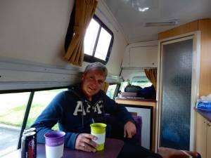 Neuseeland | Hitop Camper von Wendekreisen von Innen. Henning genießt seinen Cafe entspannt sitzend bei hohem Camper-Dach