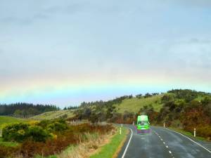 Camper on the road. Ein grüner Jucy amper fährt durch die grüne Landschaft in Neuseeland auf einen REgenbogen zu