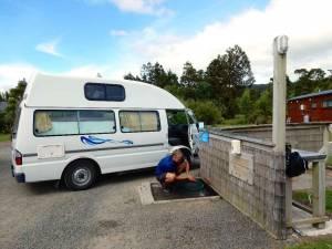 Neuseeland | Camping, Dump Station zur Entsorgung von Dreckwasser. Henning leitet mit einem Schlauch das Dreckwasser unseres Campers in den dafür vorgesehenen Abwasserkanal