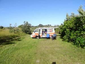 Neuseeland | Camping bei Sonnenschein, Entspannung verdient. HEnning sitzt diue Sonne genißend vor unserem Camper in einem Klappstuhl