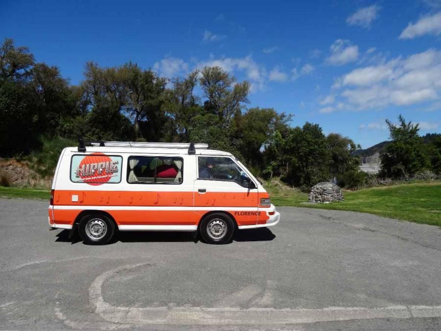 Unser Camper: Hippie, Florence. Ein kleiner VW-Bus ähnliches Auto in weiß und orange