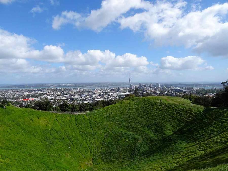 Neuseeland | Nordinsel, Panorama vom Mount Eden in Auckland über einen mit sattgrüner Wiese bewachsenen Vulkankrater auf die Skyline und den Hafen von Auckland