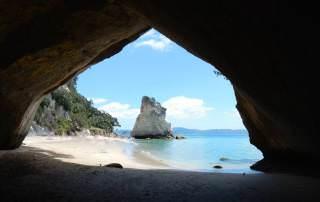 Neuseeland | Nordinsel, Cathedral Cove in der Coromandel. Blick durch die Höhle auf das türkisfarbene Meer und die Kaarststeine auf der anderen Seite. Eine der Top-Sehenswürdigkeiten & Highlights der Camping-Tour