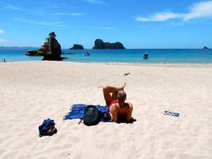 Neuseeland | Nordinsel, Entspannung am Cathedral Cove in der Coromandel. Henning liegt am weißen Strand auf einem blauen Strandtuch mit dem Blick auf das türkisfarbene Meer bei Sonnenschein