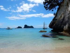 Neuseeland | Nordinsel, Panorama am Strand bei der Cathedral Cove in der Coromandel auf türkisfarbenes Wasser ein Motor- und ein Segelboot in der Bucht um geben von weißen Kaarstbergen