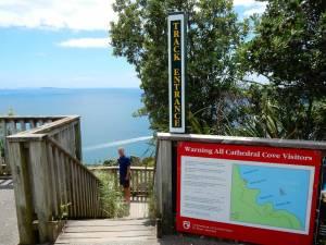 Neuseeland | Nordinsel, Startpunkt zum Cathedral Cove Track in der Coromandel. Beschreibung des Weges auf einem Schild und Henning mit dem blauen Meer im Hintergrund auf den Holztreppen die zum Weg führen