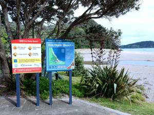 Neuseeland | Nordinsel, Regeln am Hot Water Beach in Hahei in der Coromandel. 2 Schilder erklären die heißen Quellen und das Badeverhalten, der Strand im Hintergund