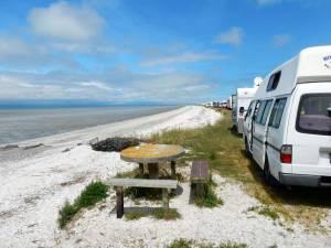 Neuseeland | Nordinsel, Miranda Rays Rest Camping in der Coromandel. Blick auf eine Schlange an Campervans direkt am Meer bei blauem Himmel