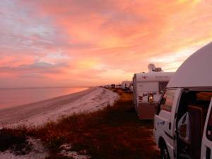 Neuseeland | Nordinsel, Miranda Rays Rest Camping in der Coromandel beim Sonnenuntergang mit Blick auf das Meer und die Reihe an Campern vor uns
