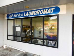 Neuseeland | Nordinsel, Laundry in Thames in der Coromandel. Blick auf die Wäscherei von außen und Henning vor den Waschmaschinen wartend im lila T-Shirt im Inneren