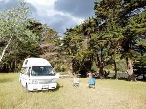 Neuseeland | Nordinsel, Simpsons Beach Campingplatz bei Whitianga in der Coromandel. Unser Camper und zwei Klappstühle stehen auf der grünen Wiese mit Blick durch Bäume auf den Strand mit schwarzen Wolken am Himmel und trotzdem Sonnenschein