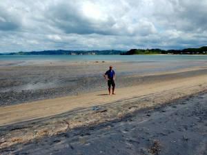 Neuseeland | Nordinsel, Ebbe am Simpsons Beach bei Whitianga in der Coromandel. Henning steht am schwarzen Vulkanstrand, das Meer türkisblau weit im Hintergrund
