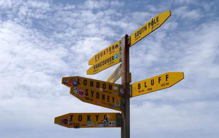 Neuseeland | Nordinsel, Hoher Norden, Weltweite Entfernungen vom Cape Reinga in Neuseeland. Gelbe Schilder in schwarzer Aufschrift vor blau-weißem Himmel. Tipps zur Entscheidung im Detail findest Du im Artikel