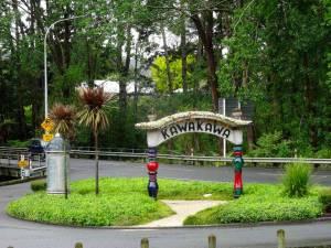 Neuseeland | Nordinsel, Kawakawa im hohen Norden. Das Ortsschild von Hundertwasser entworfen in der Mitte vor grünen Bäumen und der Straße