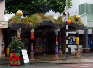 Neuseeland | Nordinsel, Eingang zu den Hundertwasser Toiletten in Kawakawa im hohen Norden. Bunte Säulen weisen Weg zu den öffentlichen WC´s