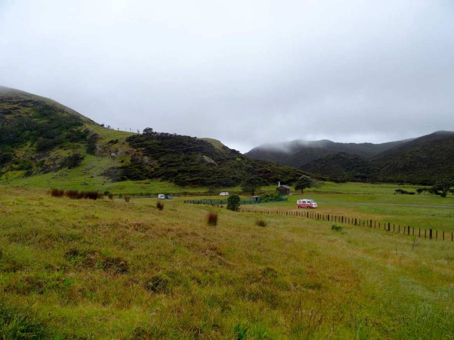 Neuseeland | Nordinsel, Spirits Bay Kapowairua Camping im hohen Norden. Blick auf den Campingplatz im grünen umzingelt von grün bewachsenen Bergen und unseren Hippie Camper