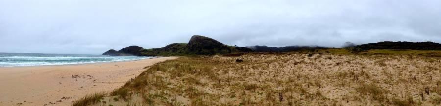 Neuseeland | Nordinsel, Panorama der Spirits Bay im hohen Norden. Blick durch die Dünen auf den Sandstrand, das wellenreiche Meer und sattgrüne bewachsene Berge im Hintergrund