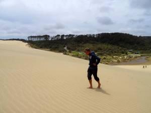 Neuseeland | Nordinsel, Hoher Norden. Mühseliger Anstieg im Te Paki Stream. Henning kämpft auf dem Weg nach oben bei den Sandbergen, die grünen Bäume im Hintergrund