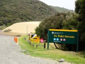Neuseeland | Nordinsel, Te Paki Stream, Hoher Norden. Schild als Wegweiser zu den Sanddünen, die im Hintergrund warten