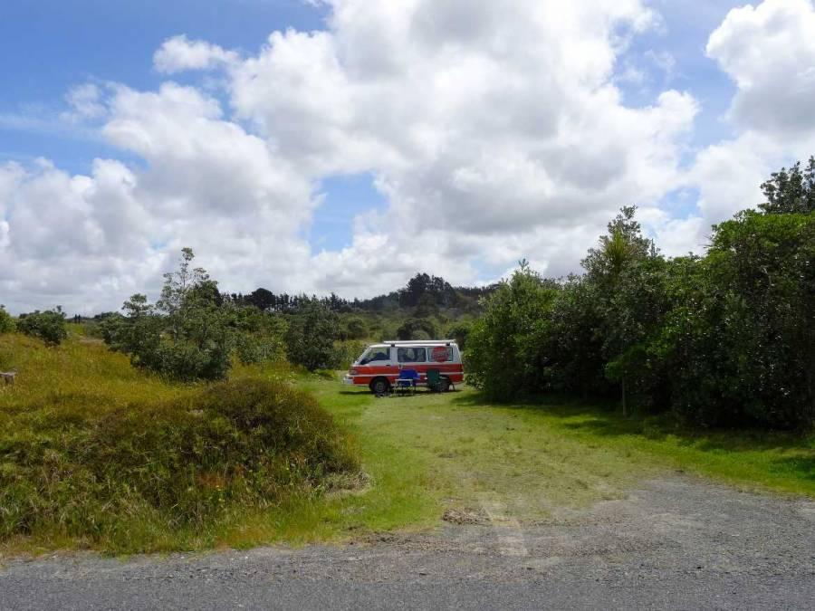 Neuseeland | Nordinsel, Unser Stellplatz auf der Uretiti Campesite im hohen Norden. Unser Hippie Camper steht umgeben von grünen Büschen auf einem idyllischen Plätzchen mit den beiden Campingstühlen im Vordergrund