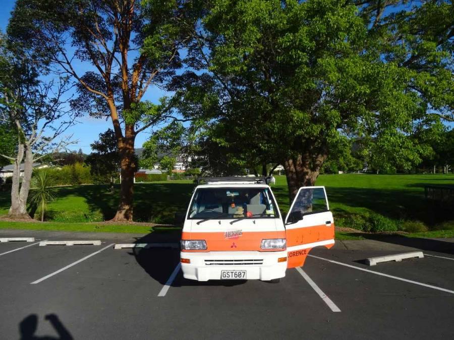 Neuseeland | Nordinsel, Camping direkt bei der iSITE in Whangarei im hohen Norden. Unser Hippie Camper steht auf dem Parkplatz mit grüner Wiese im Hintergrund unter Bäumen bei blauem Himmel und Sonnenschein