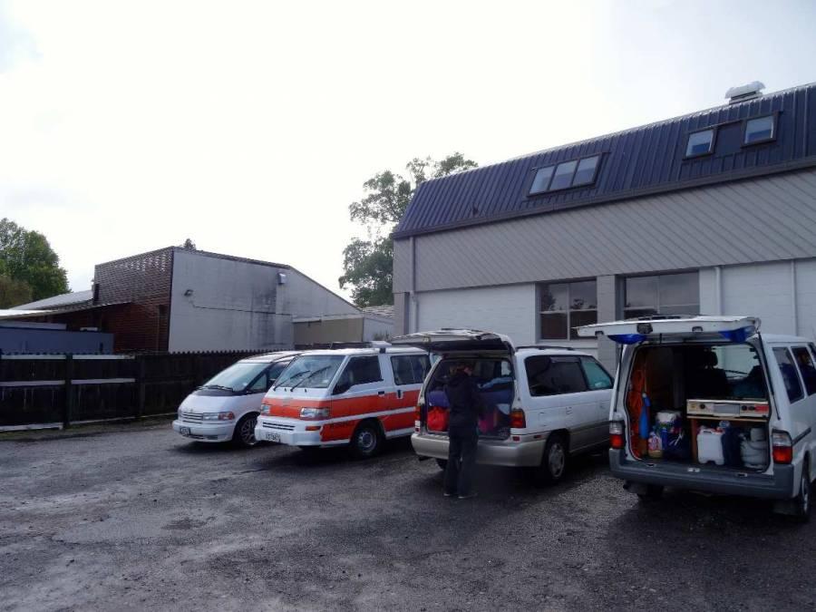 Neuseeland | Nordinsel, Parkplatz des Xbase Hostels in Rotorua . 4 Camper stehen auf einem grauen Hinterhof