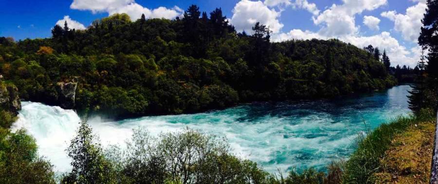 Neuseeland | Nordinsel, Panorama auf die Huka Falls in Taupo. Türkisfarbenes, reißendes Wasser des Flusses umgeben von sattgrünen Pflanzen bei blauem Himmel