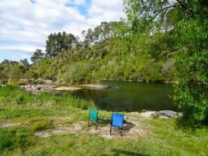 Neuseeland | Nordinsel, Rieds Farm Camping in Taupo. Unserer beiden Campingstühle in grün und blau stehen vor dem Waikato River in grüner Landschaft. Beachte unsere Tipps zum Camping