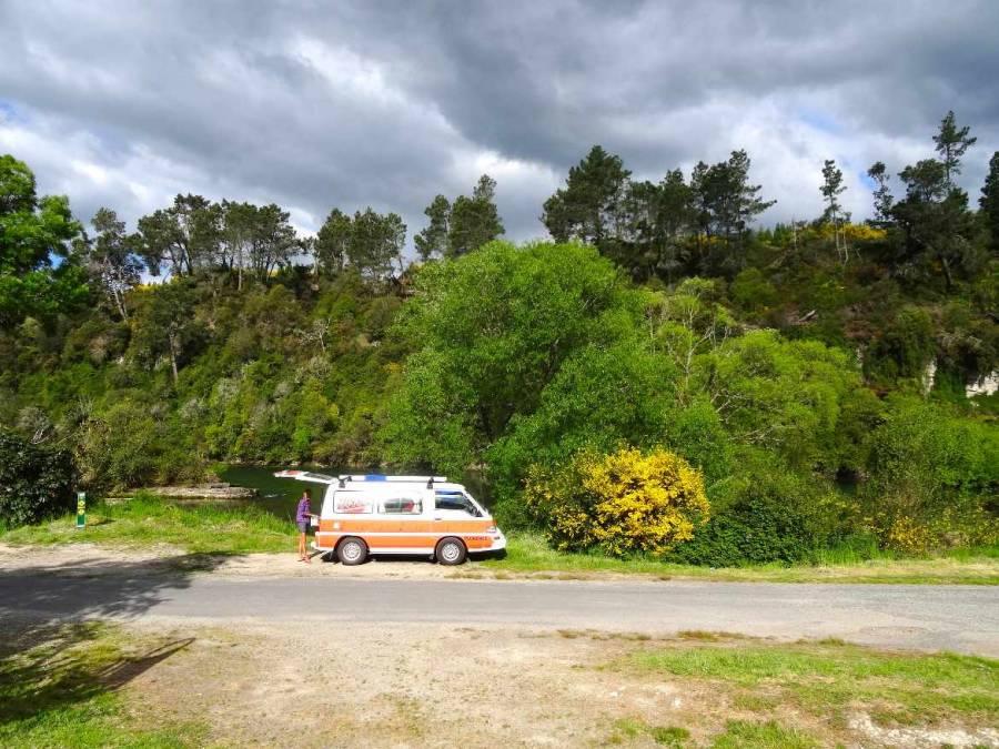 Neuseeland | Nordinsel, Einer unserer Stellplätze bei Rieds Farm Camping in Taupo. Karin steht vor unserem Hippie Camper direkt am Fluss umgeben vor grünen Büschen und Bäumen