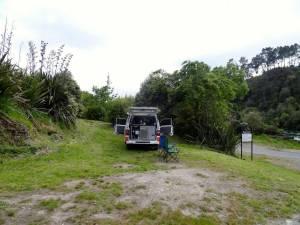Neuseeland | Nordinsel, Rieds Farm Campingplatz in Taupo. Unser Hippie Camper mit geöffneter Heckklappe und Türen auf unserem Stellplatz. Ein grüner und blauer Campingstuhl im Vordergrund vor einen sattgrünen Bepflanzung