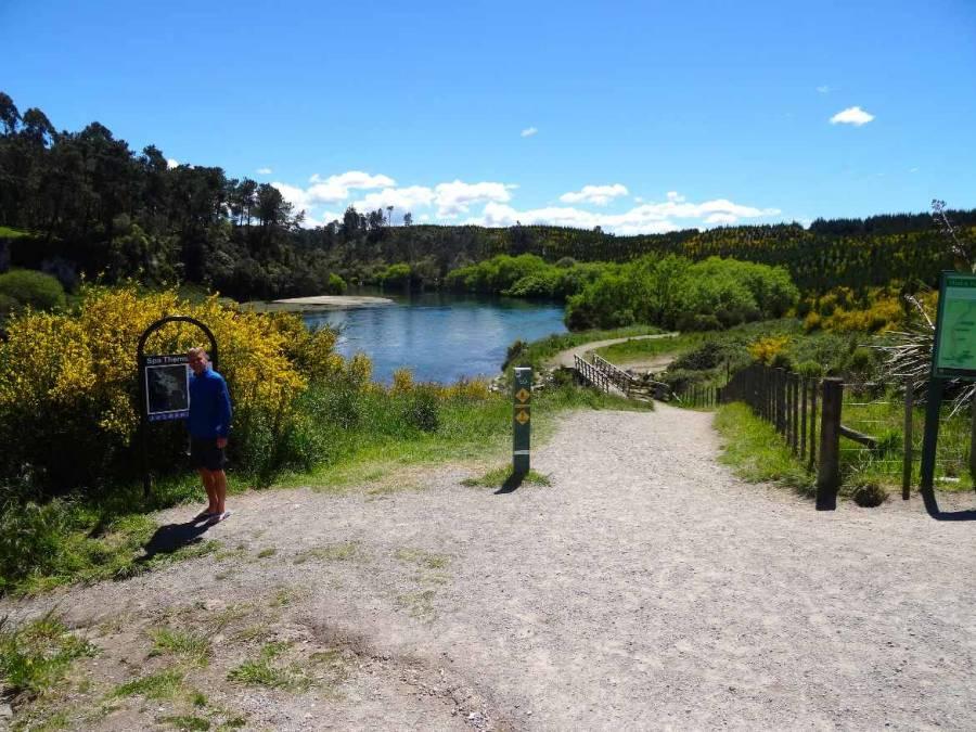 Neuseeland   Nordinsel, Spa Thermal Park and Riverbank Recreational and Scenic Reserve in Taupo. Henning am Eingang zum Reserve bei blauem Himmel mit Blick auf den Fluss, sattgrüne Landschaft mit gelben Blüten