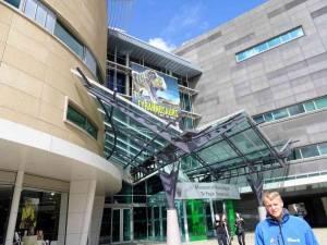 Neuseeland | Nordinsel, Eingang zum Te Papa Museum in Wellington. Henning steht vor einem modernen grauen Gebäude mit vielen Fenstern
