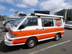 Neuseeland | Nordinsel, Parkplatz beim Te Papa Museum in Wellington. Unser orange-weißer Hippie Camper im Vordergrund andere parkende Autos vor Hochhäusern