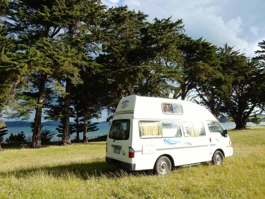 Neuseeland | Nordinsel, Unser weißer Wendekreisen High-Top-Camper am Simpsons Beach Campingplatz in Whitianga. Stellplatz mitten in einer grünen WIese mit Blick auf das türkisfarbene Meer und schwarzen Vulkansand