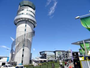 Neuseeland | Südinsel, Erste Neuseelandluft beim Warten auf den Shuttle in Christchurch am Flughafen bei Ankunft. Blauer Himmel, ein schöner Wartebereich auf einer grünen Wiese und ein Flughafentower erwarten uns am Ausgang