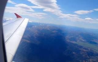 Neuseeland | Südinsel, Landeanflug Christchurch die Erste. Blick aus dem Fenster des Fliegers auf den Flügel, blauen Himmel und die schneebedeckten Alpen. Einige Tipps und den Reisebericht zur Rundreise haben wir zusammen gefasst