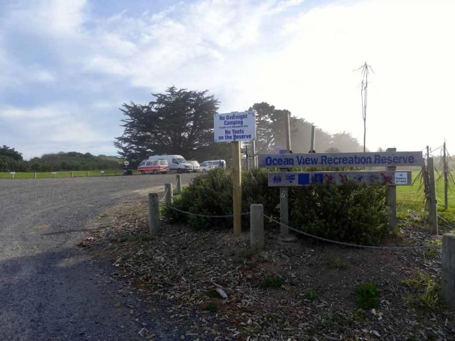 Neuseeland | Südinsel, Camping im Ocean View Recreation Reserve bei Dunedin. Blick auf die Stellplätze mit den Hinweisschildern, dass nur im gekennzeichneten Bereich Camping erlaubt ist