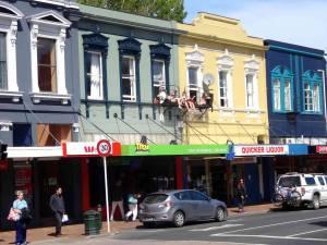 Neuseeland | Südinsel, Studentenstadt Dunedin. 4 Mädchen sitzen auf ihrem Balkon im ersten Stock vor bunten Häusern mitten auf der Hauptstraße
