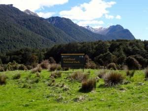 Neuseeland | Südinsel, Fiordland National Park. Ein Hinweisschild mitten auf einer grünen Wiese von Bergen umgeben