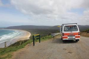 Südinsel, Florence Hill Lookout in den Catlins. Blick auf ein aufgewühltes Meer, den Strand und grünen Regenwald mit unserem orange-weißen Hippie im Vordergrund neben dem Schild Florence Hill Lookout